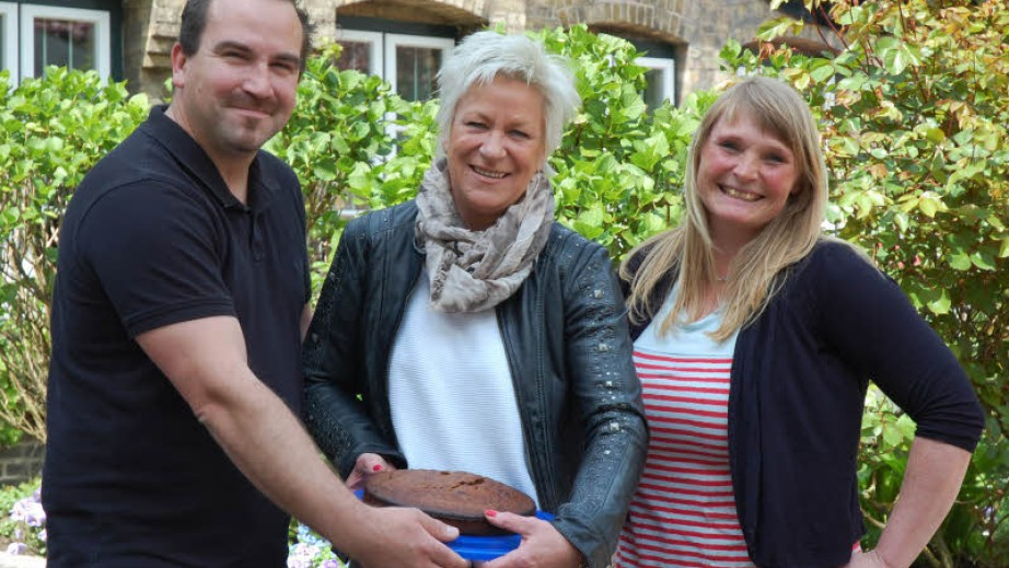 Als Dank für das neue Bad überreichte Eva Schön (r.) vom Frauenhaus einen von den Bewohnerinnen gebackenen Kuchen an Jan-Hauke Tiedemann und Silke Fischer-Tiedemann. (Foto: Müller, Quelle: www.shz.de)